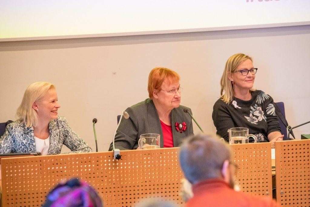 Terhi Heinilä, Tarja Halonen ja Eva Biuaudet istuvat vierekkäin ja hymyilevät.
