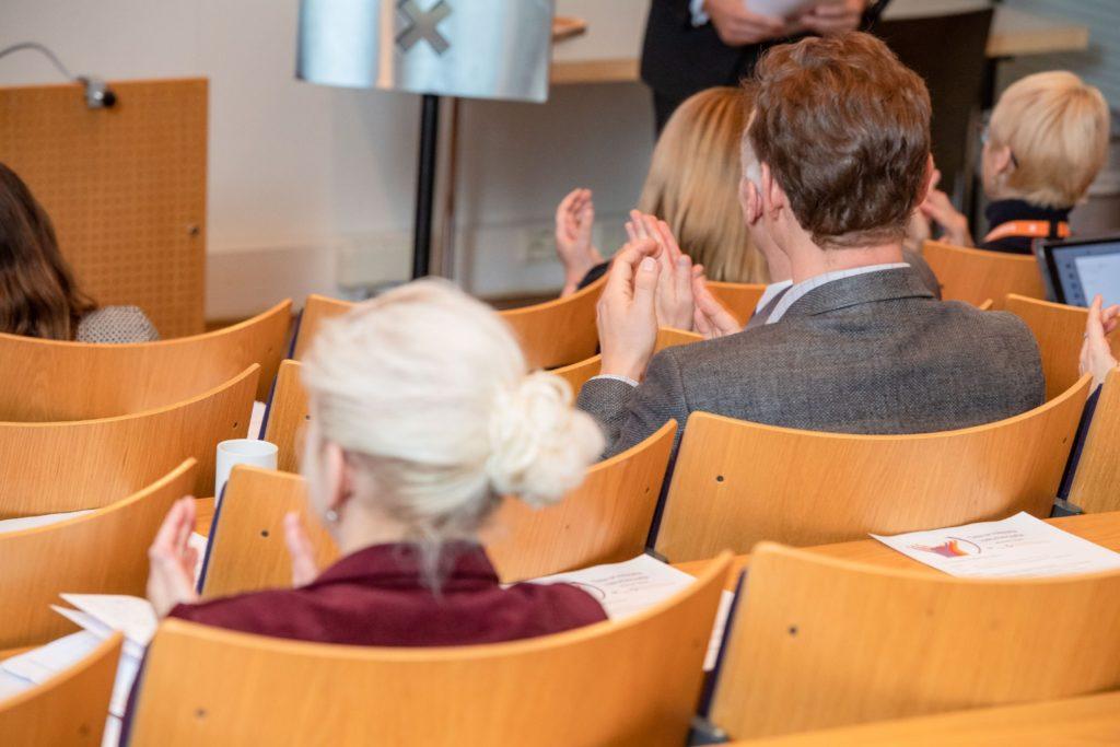 Ihmiset yleisössä taputtavat käsiään yhteen ministerin puheen jälkeen.