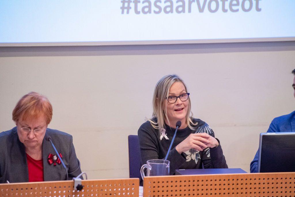Naisjärjestöjen Keskusliiton puheenjohtaja Eva Biaudet puhuu yleisölle. Vieressä istuu presidentti Tarja Halonen, joka lukee papereita.