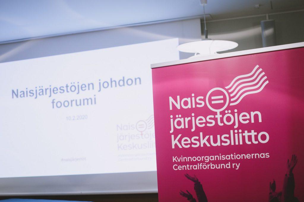Kuvassa on valkokangas, jossa lukee Naisjärjestöjen johdon foorumi