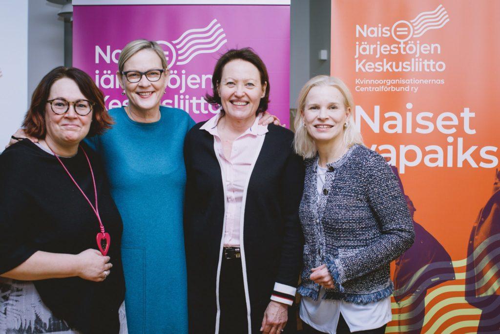 Kuvassa on neljä naista, jotka hymyilevät ja katsovat kameraan.